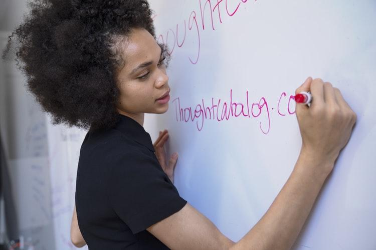 Semana Pedagógica: a imagem mostra uma mulher negra e jovem escrevendo em um quadro branco. Ela usa camisa de manga curta preta, cabelo solto e crespo e escreve com uma caneta de cor vermelha.