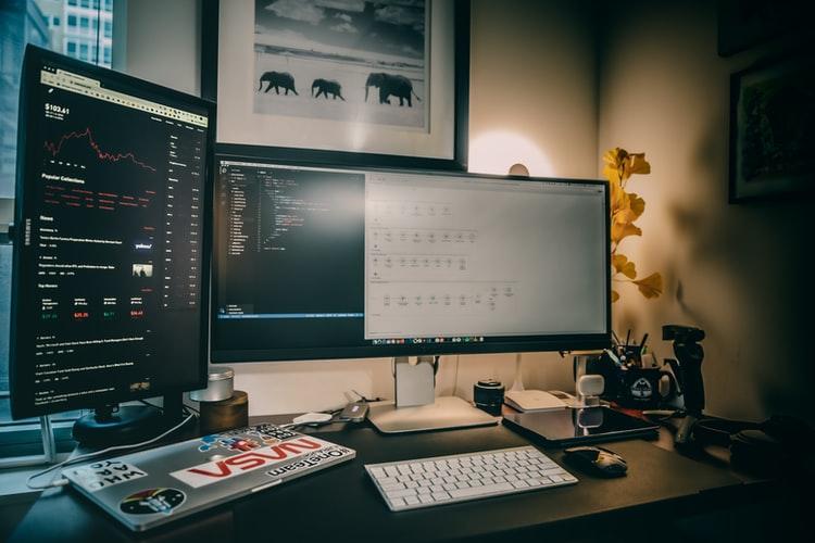 Vagas home office: imagem mostra um pequeno escritório improvisado em casa, com diversos computadores com gráficos em cima de uma mesa. Atrás da mesa há um quadro preto e branco e, por trás dos computadores, uma luminária.