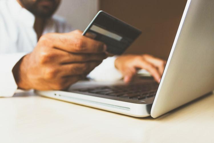E-commerce: na imagem, um par de mãos segura um cartão de crédito em frente a um computador. Não é possível ver o rosto do comprador.